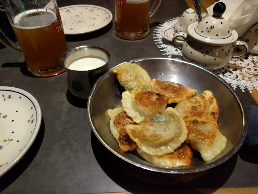 Pan-fried spinach pierogies with blue cheese cream topping.